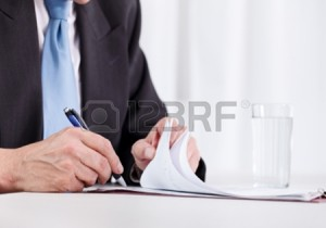 14351898-business-man-hand-writing-on-paper-close-up